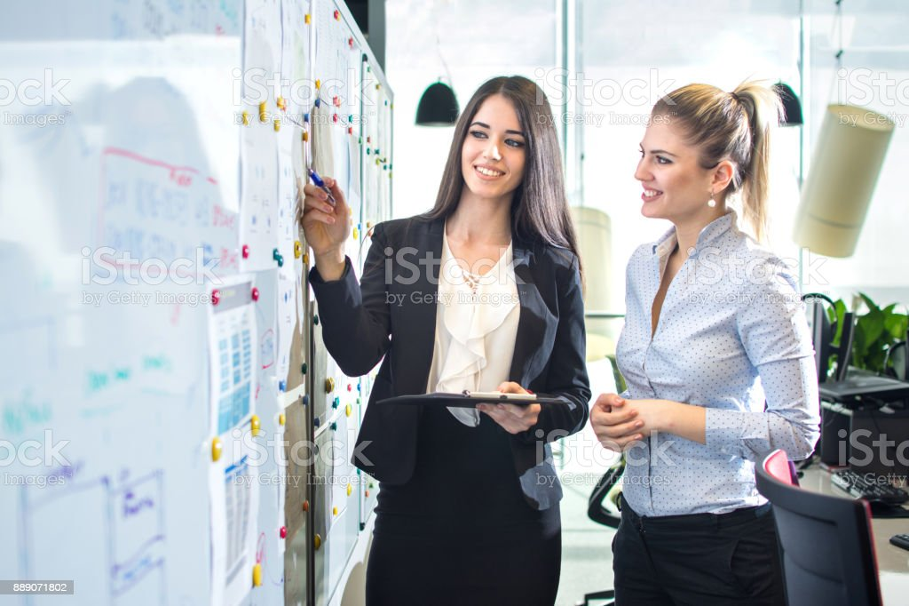 Business woman having a presentation in front of white board. stock photo