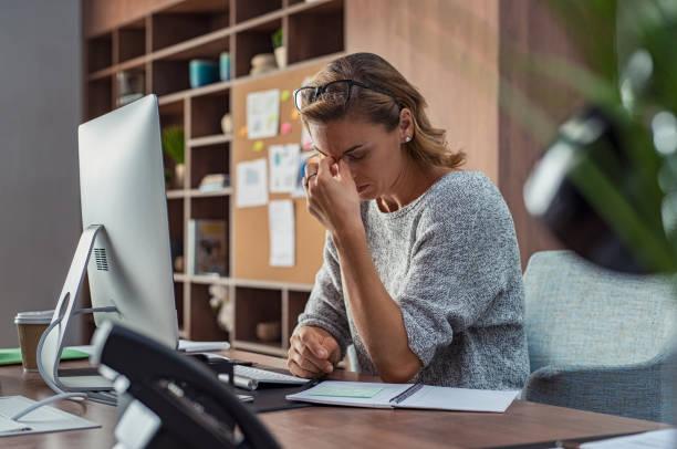 business-frau mit kopfschmerzen im büro - verzweiflung stock-fotos und bilder