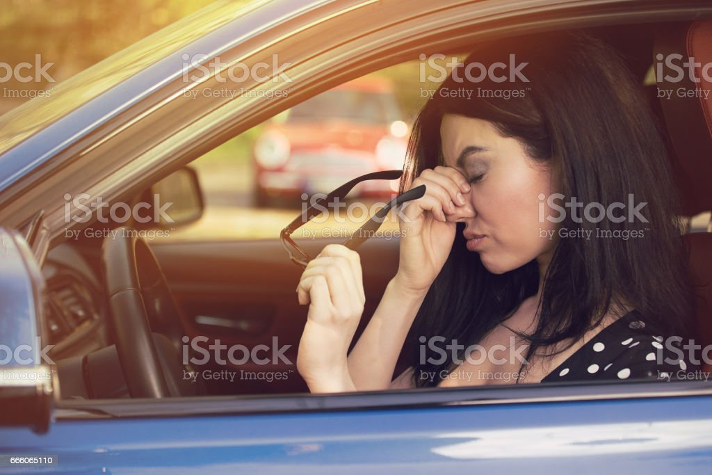 Business woman having headache taking off her glasses has to make a stop after driving car stock photo