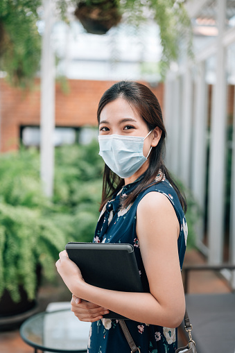 Business woman hold a laptop while standing on the property business background wear protect facemask to prevent PM2.5 dust and smog protect from air pollution and infectious diseases in bangkok thailand