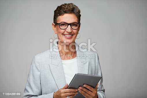 istock Business woman holding a digital tablet and wearing glasses. 1159438169