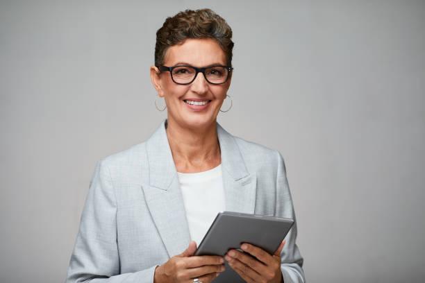 Geschäftsfrau hält ein digitales Tablet und trägt eine Brille. – Foto