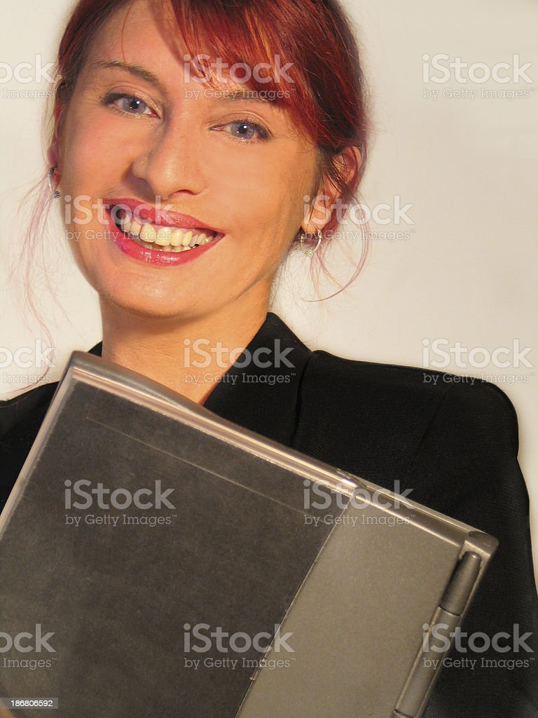 Business woman holding a laptop and smiling royalty-free stock photo