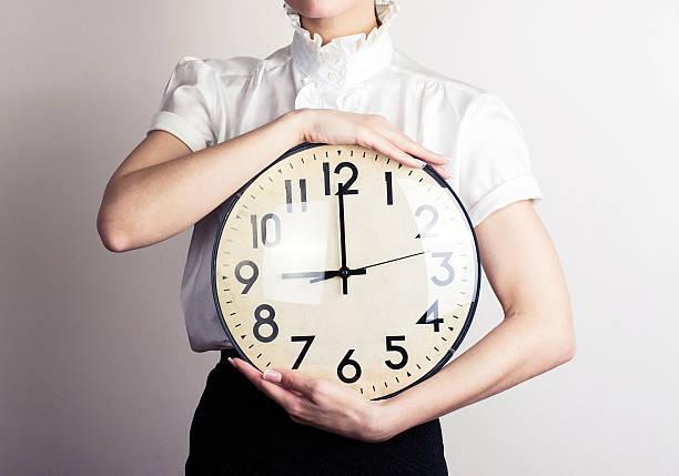 femme d'affaires tenant une horloge - pendule photos et images de collection