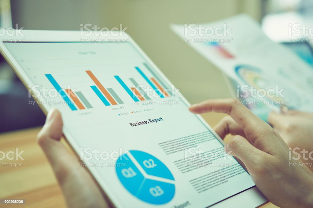 Business woman holding a tablet screen financial summary. To present to the team. stock photo