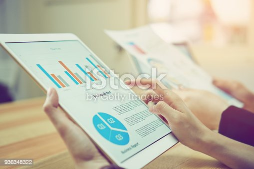 istock Business woman holding a tablet screen financial summary. To present to the team. 936348322
