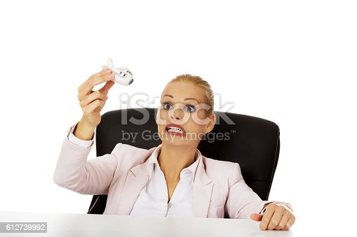 Business woman sitting behind the desk and holding a toy plane.