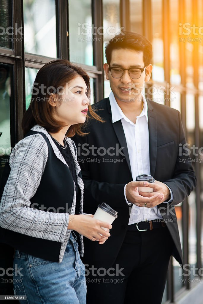 Business woman holding coffee cup and talking with her team outdoor....