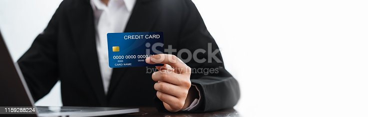 1016971522 istock photo Business woman holding credit card and laptop computer with shopping online. Pay online for convenience 1159288224