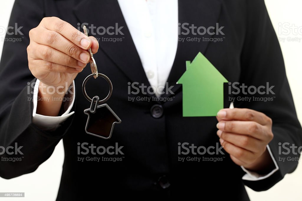 Business woman holding house key and house shape stock photo