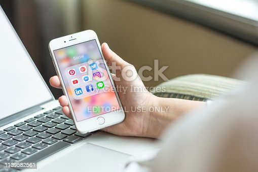 istock Business woman holding iphone smartphone  with icons of social media on screen as relaxing lifestyle, internet technology in everyday life 1139582561