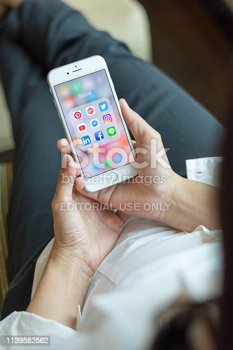 istock Business woman holding iphone smartphone  with icons of social media on screen as relaxing lifestyle, internet technology in everyday life 1139582562