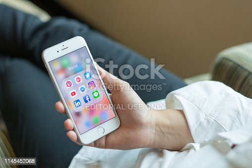 istock Business woman holding iphone smartphone  with icons of social media on screen as relaxing lifestyle, internet technology in everyday life 1145452068