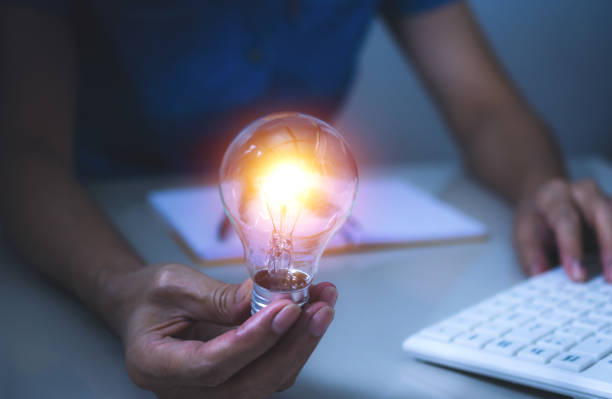 Business woman holding light bulb on the desk in office and using  computer in  financial,accounting,energy,idea concept. - foto stock