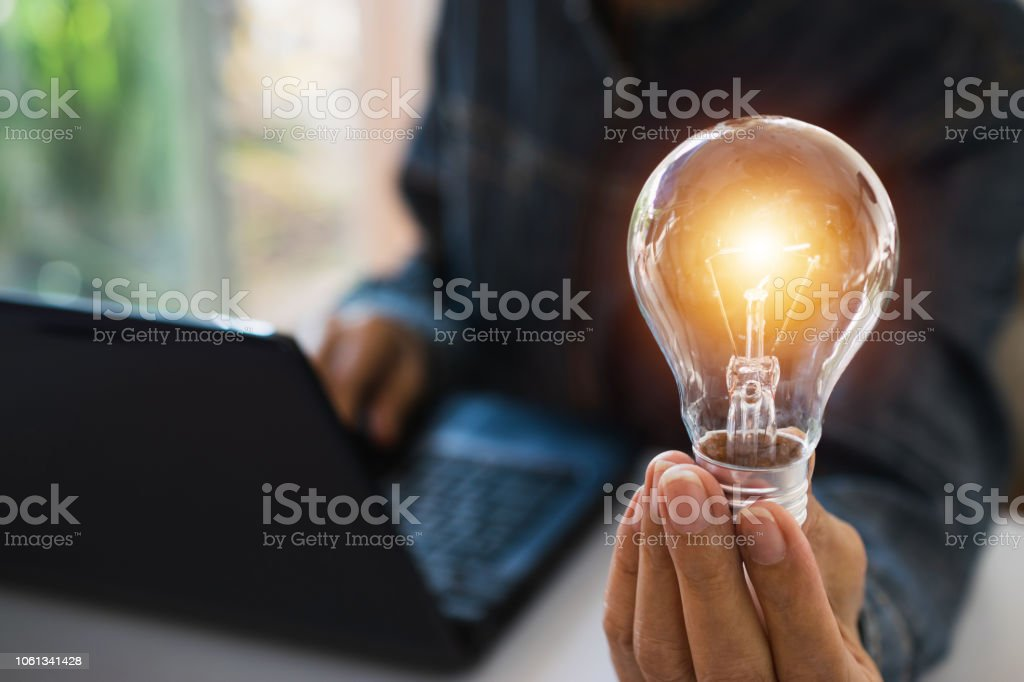 Business woman holding light bulb on the desk in office and using  computer in  financial,accounting,energy,idea concept. stock photo
