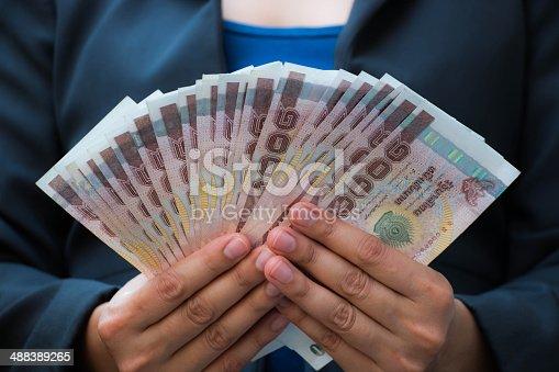 488389267istockphoto Business woman holding money 488389265