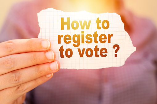 business woman holding tear paper with how to register to vote ?