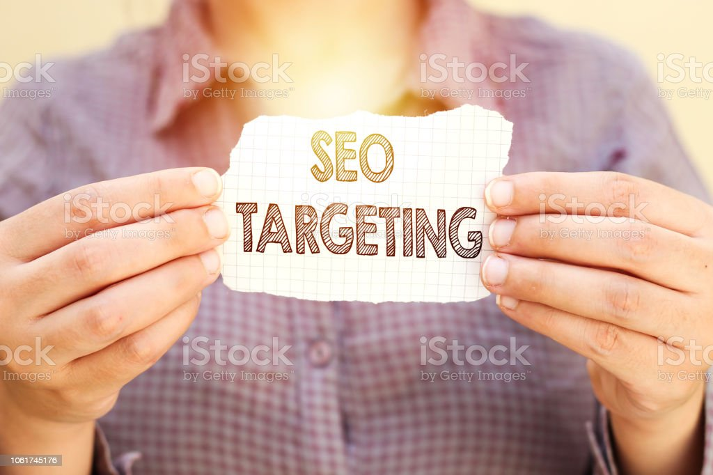business woman holding tear paper with SEO targeting text – zdjęcie