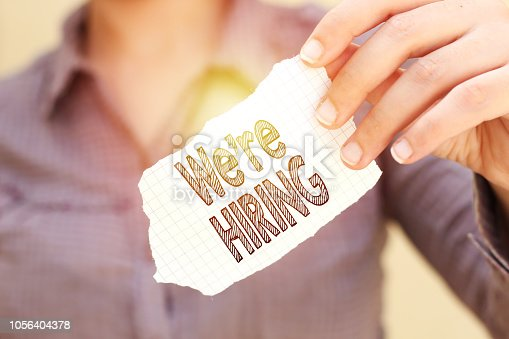istock business woman holding tear paper with we're hiring text 1056404378