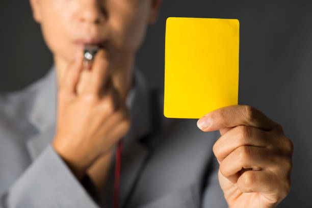 Business woman holding yellow card and blowing a whistle stock photo