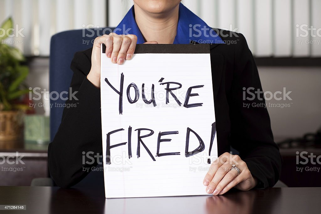 Business Woman Holding 'You're Fired' Sign at Desk stock photo