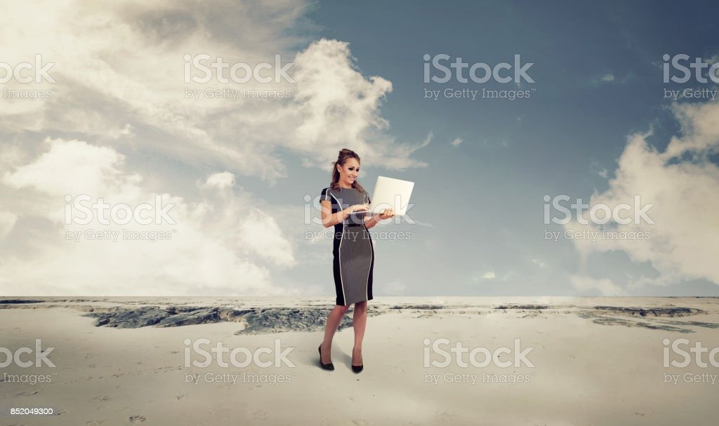 Business woman in a desert using a laptop computer stock photo