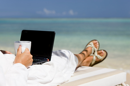 unrecognizable businesswoman in a robe with morning coffee working on laptop computer at a beach