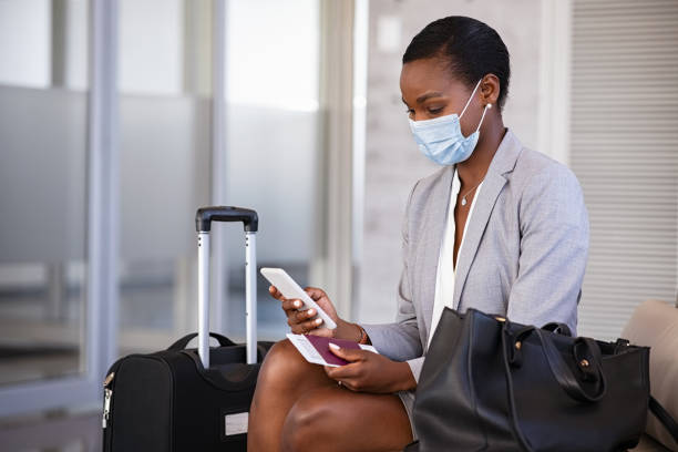 Business woman in airport with face mask checking phone stock photo