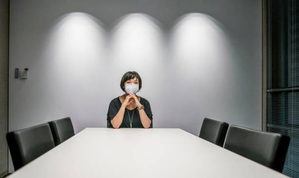 Geschäftsfrau in einem leeren Sitzungssaal im Büro trägt eine Gesichtsmaske, um COVID-19 zu vermeiden – Foto