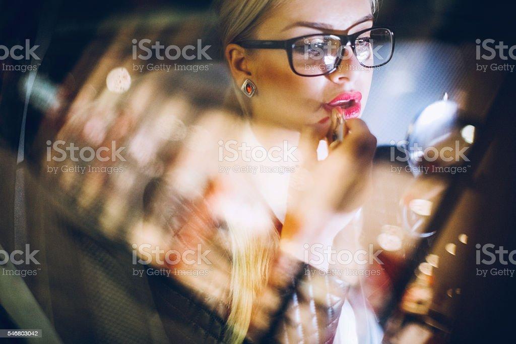 Business woman in car on Paris streets putting lipstick on - foto de acervo