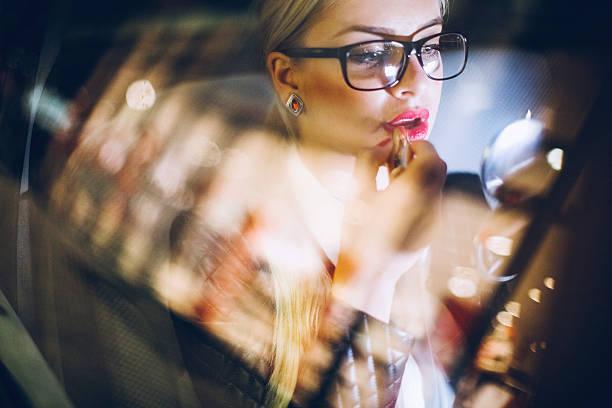 business woman in car on paris streets putting lipstick on - anzieh nacht stock-fotos und bilder