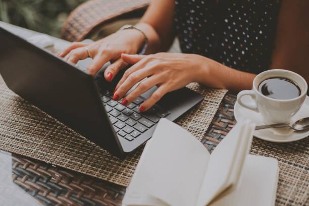 geschäftsfrau in kaffeesatz auf einem laptop aus nächster nähe - drehbuchautor stock-fotos und bilder