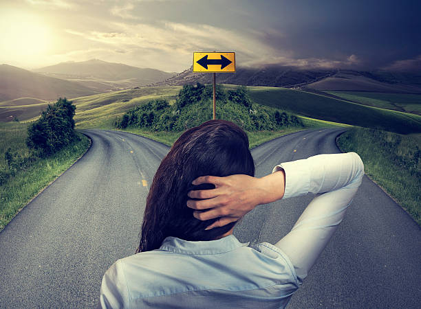 business woman in front of two roads thinking deciding stock photo