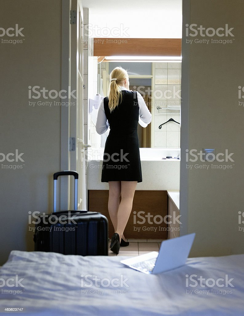 Business woman freshening up after arrival in hotel room, in front of...