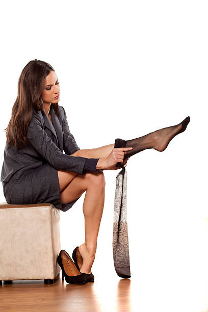 business woman in jacket and skirt puts on nylon stockings - black women wearing pantyhose stock photos and pictures