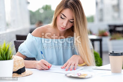 istock A business woman, in summer in a cafe restaurant, fills in a written contract, puts a signature on contract, making a transaction, certifying the document. Legal services, paperwork and document. 1149598140