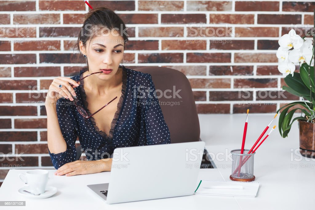 Business woman in the office at the desk with laptop thinking zbiór zdjęć royalty-free
