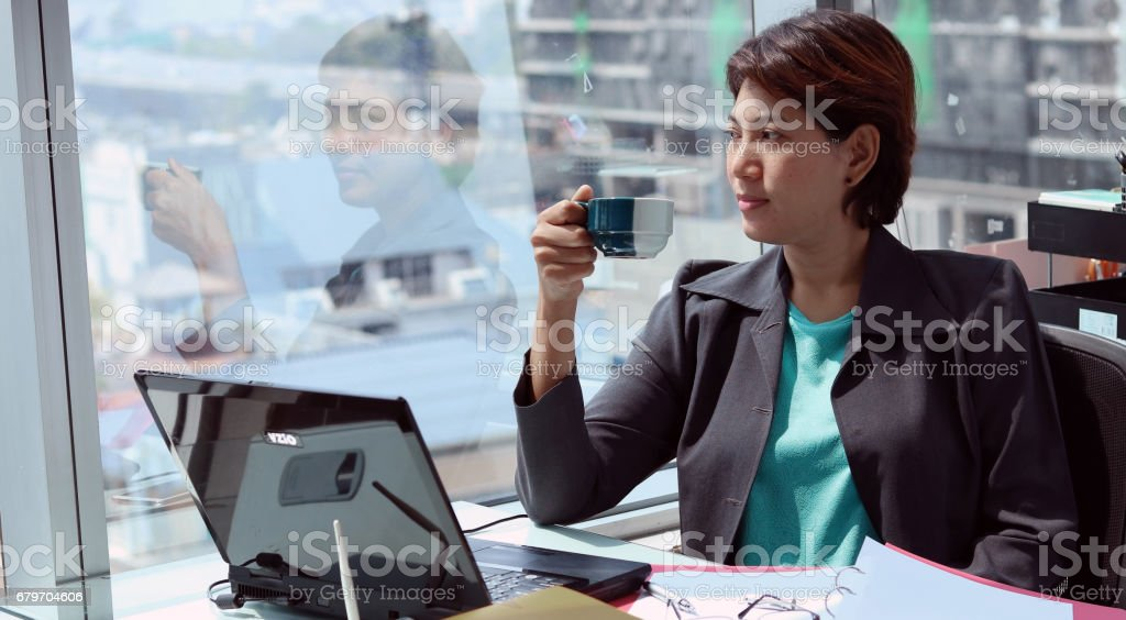 Business woman in the office with views of window and coffee cup stock photo