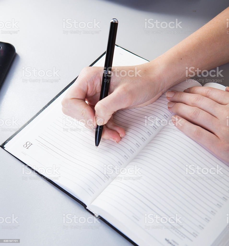 business woman in the workplace does records in a diary stock photo