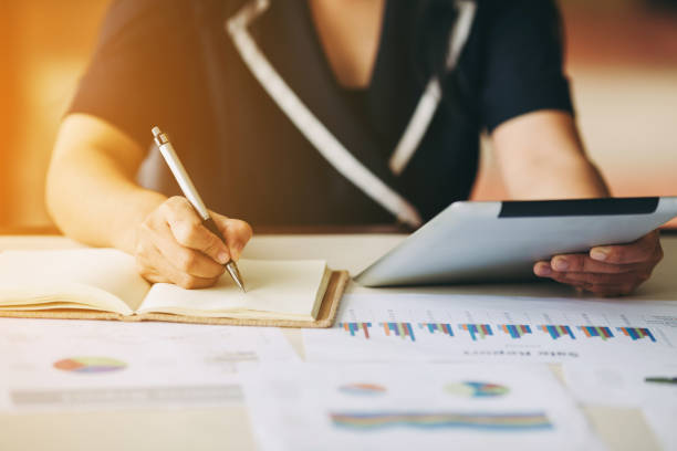 Business woman investment consultant analyzing company annual financial report balance sheet statement working with documents graphs. stock photo