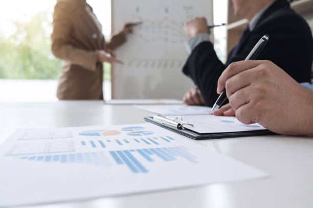 Business woman leader making presentation with her colleagues, pointing to the graph on board and business strategy during meeting in modern office stock photo