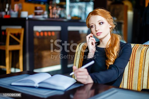 694187664istockphoto Business woman leading business conversation on the phone in restaurant. 1020095396