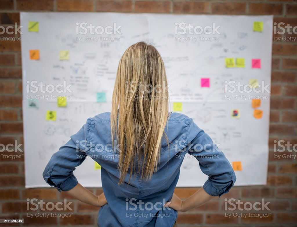 Business woman looking at a wall chart Casual business woman working at a creative office and looking at a wall chart Adhesive Note Stock Photo