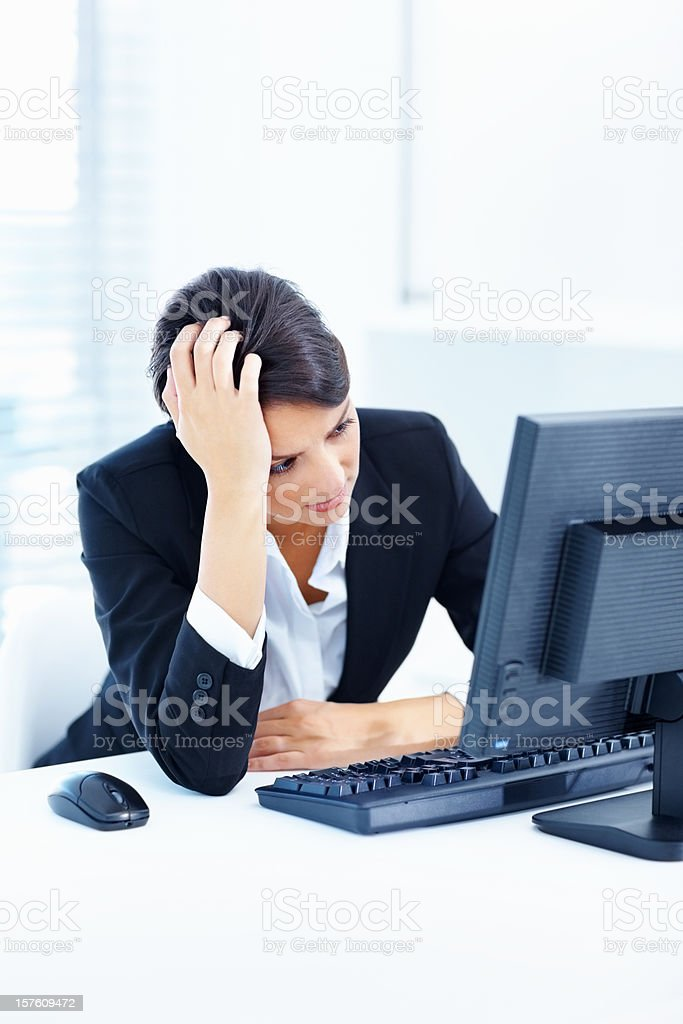 Business woman looking at computer monitor with hand on head royalty-free stock photo