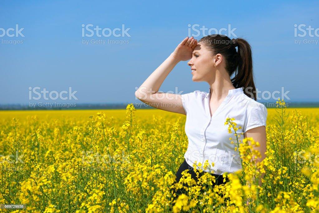 Mulher de negócios olhando para a distância. Jovem menina no campo de flor amarela. Paisagem linda primavera, dia ensolarado, colza - foto de acervo