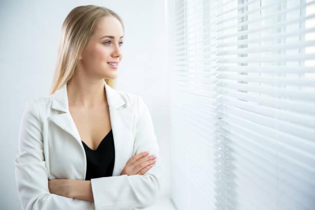 femme d'affaires regardant par la fenêtre - cosmetique store photos et images de collection