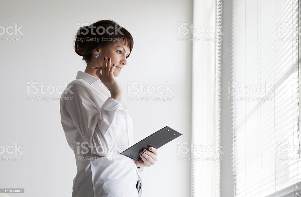 business woman looks out the window royalty-free stock photo
