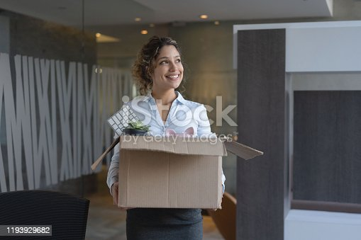 Happy business woman moving into a new office and carrying her belongings in a box