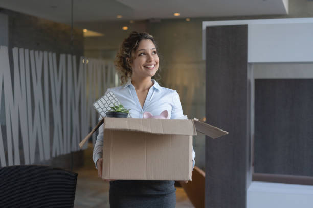 Business woman moving into a new office Happy business woman moving into a new office and carrying her belongings in a box quitting a job stock pictures, royalty-free photos & images