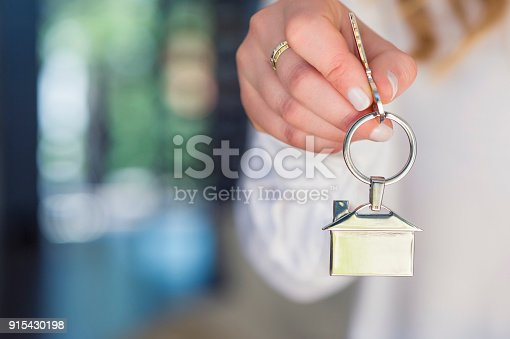 istock Business Woman offering a house key. 915430198